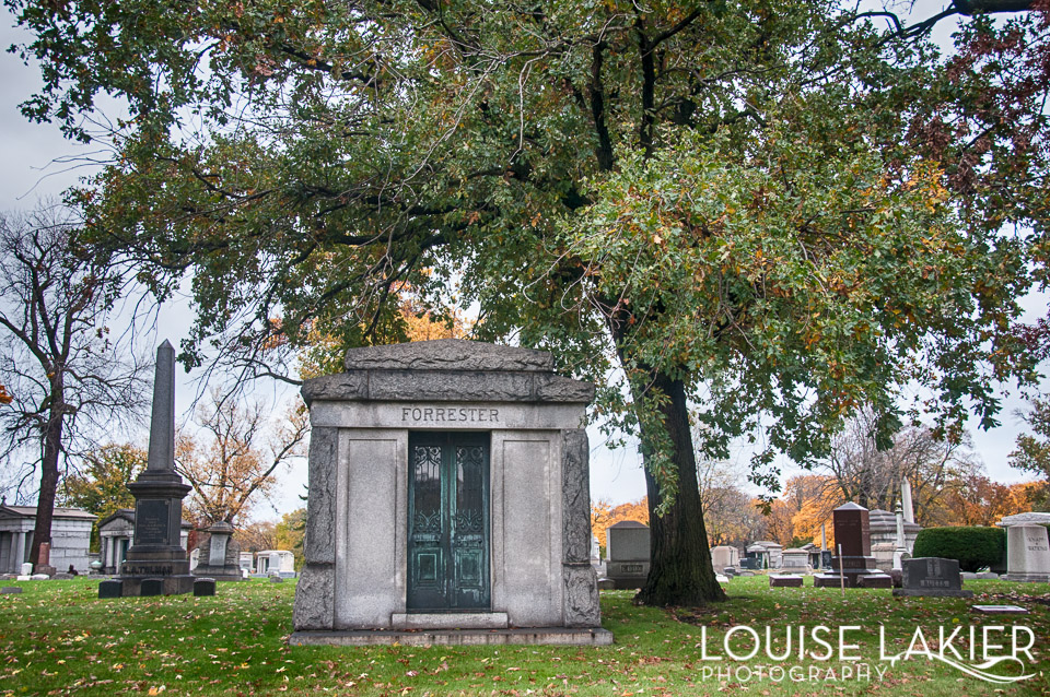 A mausoleum under a tree in Oakwoods Cemetary